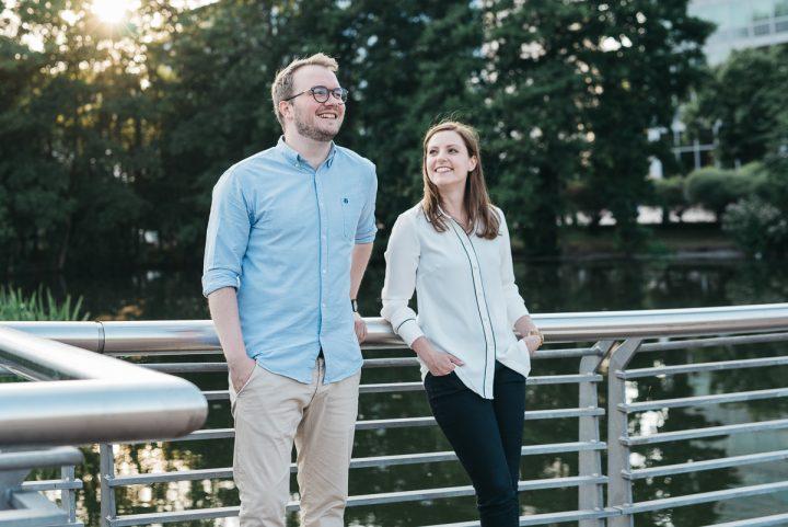 Über uns: zu sehen sind die Gründer Marius und Nina, die an einem Brückengeländer lehnen. Marius steht von uns aus gesehen links neben Nina. Er trägt ein hellblaues Hemd und eine helle beige Hose. Er trägt eine braune, runde Brille und lacht. Seine rechte Hand steckt in seiner Hosentasche, seine Linke stützt sich auf das Brückengeländer. Nina schaut Marius an und trägt eine weiße Bluse sowie eine schwarze Hose. Ihre Hände stecken in den Hosentaschen.