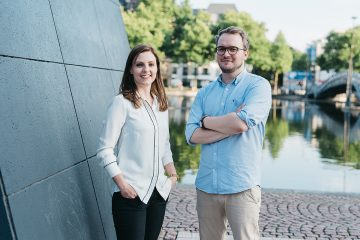 Die beiden Gründer Marius und Nina. Nina steht von uns aus gesehen links neben Marius und hat ihre Hände in den Hosentaschen. Sie trägt eine weiße Bluse, sowie eine schwarze Hose. Sie lächelt leicht schräg stehend in die Kamera. Marius hat die Arme vor dem Oberkörper verschränkt und trägt ein hellblaues Hemd, sowie eine helle beigefarbene Hose. Er trägt eine braune, runde Brille und schmunzelt in die Kamera. Sie stehen beide vor dem Weiher im Meidapark in Köln.