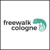 Das Logo der Firma Freewalk Cologne, Partner von aloove. in schwarzen Lettern steht Freewalk und nach links versetzt Cologne untereinander. Rechts daneben befindet sich ein türkisfarbenes Chamäleon, das seinen Schwanz unter seinen Füßen eingerollt hat. Das Ende des Schwanzes zeigt die beiden Spitzen des Kölner Doms.