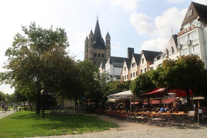 Die Altstadt von Köln. Rechts sieht man den Außenbereich diverser Lokalitäten. Im Hintergrund ist die Kirche Groß St. Martin zu sehen. Aufgenommen für das Paket Stadttour mit Heiratsantrag.