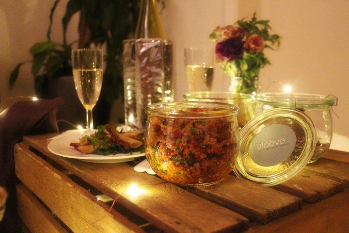 Speisen für ein romantisches Picknick oder einen Indoorpicknick Heiratsantrag. Couscous- und Nudelsalat auf einer Weinkiste, die als Tisch genutzt wird. Eine Flasche Sekt mit zwei Gläsern und einem kleinen Blumenstrauß stehen auch auf der Kiste.