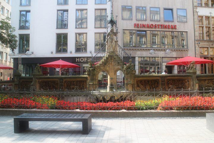 Frontalaufnahme des Heinzelmännchen Brunnens. Die Blumen im Vordergrund blühen rot und gelb. Während der Stadtführung Köln aufgenommen.