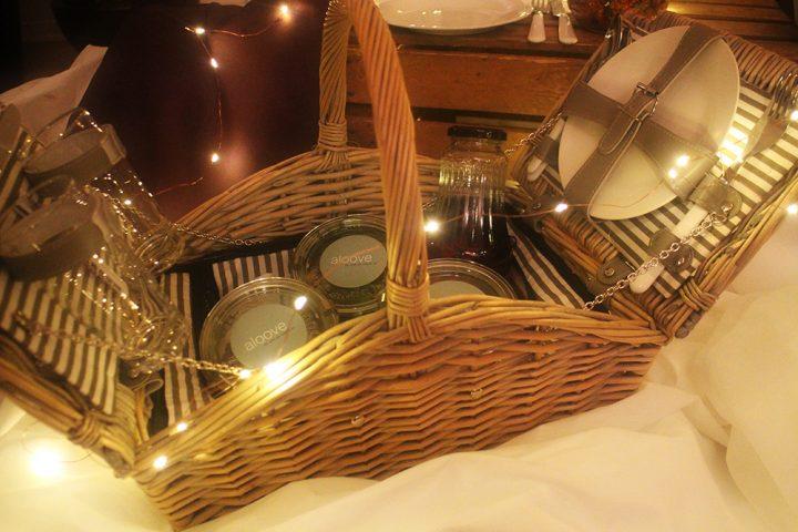 Picknickkorb für ein romantisches Picknick oder einen Indoorpicknick Heiratsantrag. Er ist gefüllt mit Weckgläsern und einer Glasflasche.