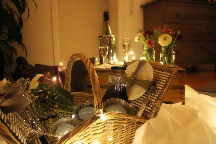 Picknickkorb gefüllt mit Weckgläsern, einer Glasflasche und einem Strauß Blumen, im Vordergrund. Eine Weinkiste, die als Tisch genutzt wird, mit einer Flasche Sekt, zwei Sektgläsern und Blumendekoration im Hintergrund. Bild für den Indoorpicknick Heiratsantrag.