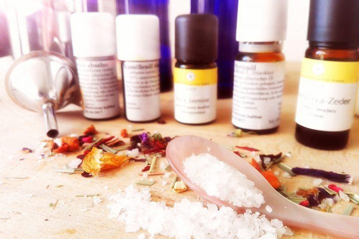Verschiedene Ätherische Öle und ein Holzlöffel mit Salz im Vordergrund. Utensilien für den Naturkosmetik Workshop. Kosmetik selber machen ist so ganz einfach.