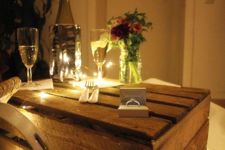 Verlobungsring auf einer Weinkiste, die als Tisch genutzt wird. Darauf stehen Blumen und eine Flasche Sekt mit zwei Gläsern. Aufgenommen für das Paket Indoorpicknick Heiratsantrag.
