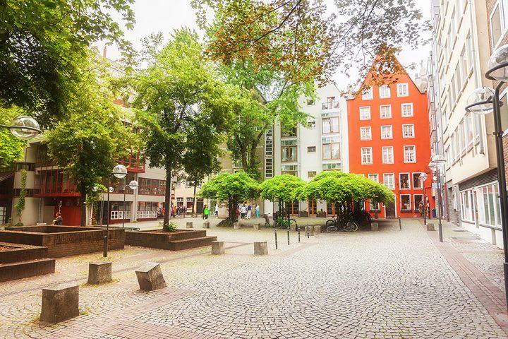Auf der Stadtführung Köln zu sehen. Der Platz mit dem Tünnes und Schäl Denkmal. Im Hintergrund, ist ein rotes Haus zu sehen. Die Bäume tragen grüne Blätter und der Platz ist menschenleer.