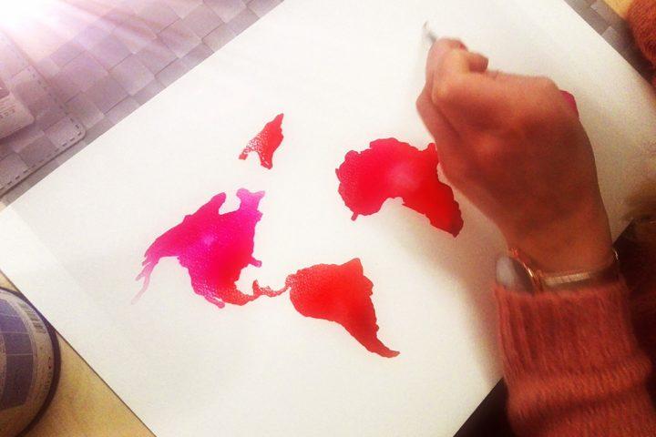 Eine Hand, die einen Pinsel hält und eine rote Weltkarte malt. Entstanden im Malkurs.