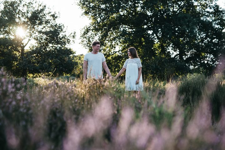 Aufnahme bei einem Paarshooting. Ein Pärchen steht nebeneinander und hält sich an den Händen fest. Sie schauen sich dabei in die Augen. Er trägt ein weisses T-Shirt, sie ein weisses Kleid mit Spitze am Ausschnitt und den Armen. Beide stehen auf einer Wiese mit Bäumen im Hintergrund.