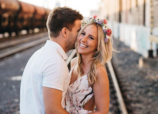Fotografie aus einem Paarshooting. Ein Mann und eine Frau umarmen sich. Er trägt ein weisses Poloshirt und eine helle, blaue Jeans. Sie ein helles Kleid mit floralem Muster. Sie hat einen Blumenkranz in den Haaren. Er steht links und hat sein Gesicht hinter ihrem Kopf vesteckt. Sie lacht und sieht sehr glücklich aus. Die Location ist ein Bahnhof. Im Hintergrund ist verschwommen ein Güterzug zu sehen. Beide stehen auf Schienen.