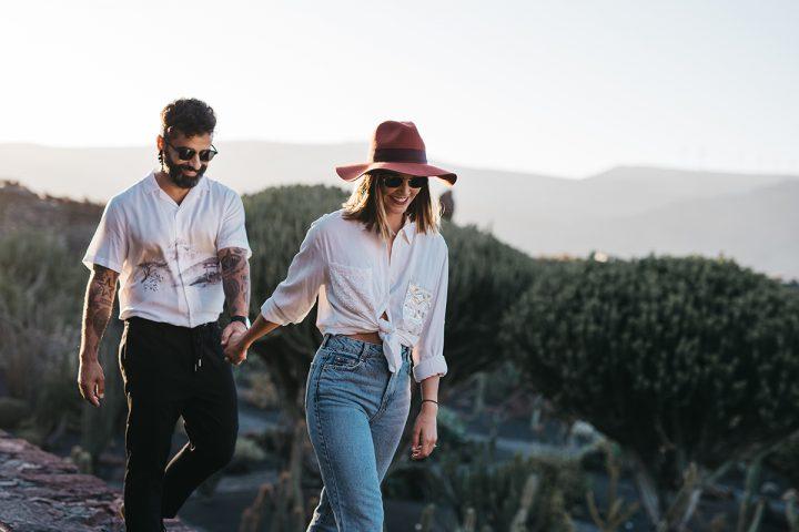 Paar bei einem Paarshooting. Beide befinden sich in der Natur. Er trägt ein weisses Hemd mit einem Aufdruck, eine dunkle Hose und eine Sonnenbrille. Sie trägt einen braunen Hut, eine Sonnenbrille, eine weisse Bluse, die sie mit einem Knoten vorne zusammengebunden hat und eine hellblaue Jeans. Sie geht vor ihm und hält seine Hand. Beide lächeln.