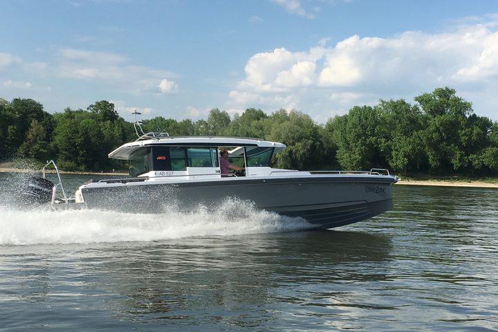Ein Boot auf dem Rhein. Es ist ein Schnellboot, das unten grau und oben weiß ist. Es hat ein Dach und ein Mann steuert es bei einer Bootsfahrt Köln. Das Wetter ist schön, der Himmel ist blau.