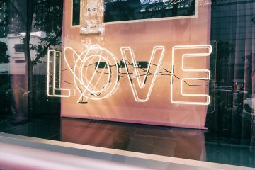 Ein Schaufenster mit dem Leuchtschriftzug Love. Dabei ist durch das O ein Herz geschlungen. Das Bild für ein Date in Köln.