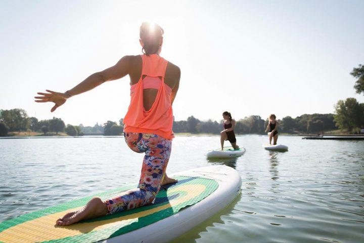Drei Frauen beim SUP Köln mit Yoga auf einem See. Im Vordergrund ist eine Frau in bunter Sportkleidung, auf einem Paddleboard zu sehen. Sie kniet auf dem Board und ihr linker Arm zeigt nach hinten. Sie ist von hinten zu sehen. Sie blickt in Richtung zweier Frauen, die in ihre Blickrichtung auf ihren Paddleboards knien. Die linke Frau trägt Sportkleidung, die rechte Frau einen dunkeln Badeanzug. Das Wetter ist schön, die Sonne scheint.