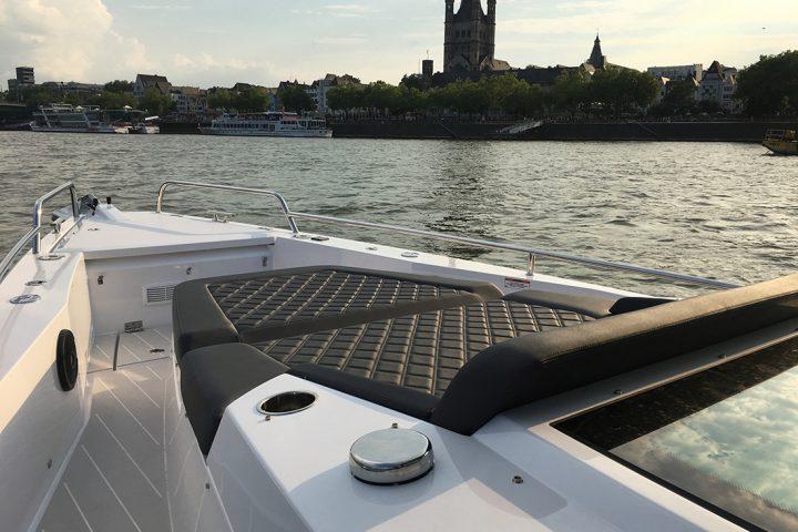 Eine Bootsfahrt Köln. Der Bug eines weißen Bootes, mit einer schwarzen Liegefläche. Im Hintergrund ist die Kirche Groß St. Martin in Köln zu sehen. Ebenfalls zwei größere Schiffe.