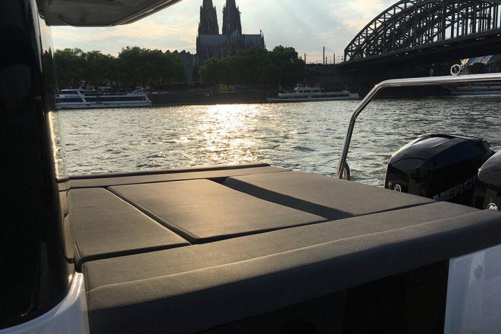 Eine Bootsfahrt Köln. Die Liegefläche eines Bootes ist zu sehen. Sie ist schwarz. Rechts am äußeren Bildrand ist der Motor zu sehen. Im Hintergrund, auf der rechten Bildseite ist die Hohenzollernbrücke zu sehen. Mittig im Hintergrund der Kölner Dom.