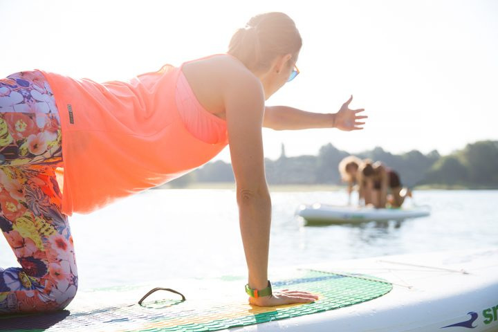 Im Vordergrund ist eine Frau auf einem Paddleboard zu sehen. Sie kniet im Vierfüßlerstand auf dem Board und hebt ihre linke Hand waagerecht nach vorne. Sie trägt bunte Sportkleidung und eine Sonnenbrille. Sie blickt in Richtung zweier Frauen, die ebenfalls auf ihren Boards knien. Sie sind nur verschwommen zu erkennen. Das Wetter ist schön, die Sonne scheint. Das Bild entstand beim SUP Köln mit Yoga auf dem See.