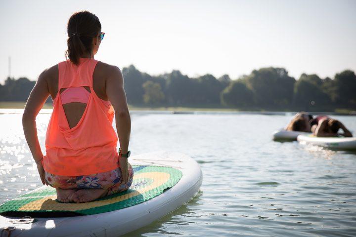 Vorne links in Bild ist eine Frau in bunter Sportkleidung zu sehen. Sie kniet auf einem Paddleboard und blickt zu zwei Frauen. Wir sehen sie von hinten. Die beiden Frauen sitzen auf ihren Knien und sind nach vorne auf ihr Paddleboard gebeugt. Das Bild entstand beim SUP Köln mit Yoga am See, bei sonnigem Wetter.