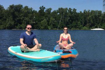 SUP Yoga auf dem See. Links ist ein Mann zu sehen. der im Schneidersitz auf einem türkisfarbenen SUP Board sitzt. Er trägt eine Sonnenbrille, ein dunkelblaues T-Shirt und eine schwarze kurze Hose. Rechts im Bild sitzt eine Frau in einem weiß-rot gestreiften Bikini, ebenfalls auf einem SUP Board. Es ist blau- orange. Sie trägt ebenfalls eine Sonnenbrille. Der Himmel ist blau und die Sonne scheint.