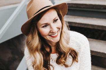 Eine Frau mit einem hellbraunen Hut und rotem Lippenstift. Sie lächelt schräg in die Kamera. Sie trägt ihre Haare lockig über beide Schultern. Sie trägt einen weißen Pullover und sitzt auf einer Treppe. Sie ist Fotografin für eine Hochzeit.