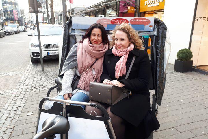 Zwei glückliche Frauen in einer Rikscha. Stadtrundfahrt mit einer Rikscha Köln.