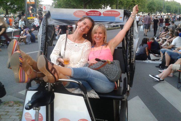 Zwei fröhliche Frauen in einer Rikscha, mit vielen Menschen im Hintergrund. Bild für die Stadtrundfahrt Rikscha Köln.