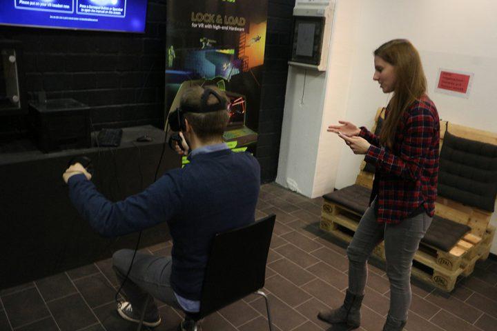 Mann und Frau beim Virtual Reality Spiel. Links sitzt ein Mann im dunkelblauen Pullover und grauer Jeans auf einem Stuhl. Er hält Controller in den Händen und hat eine Virtual Reality Brille aufgesetzt. Vor ihm befindet sich ein Fernseher an der Wand. Rechts von dem Mann steht eine Frau mit einm rot-blau Karierten Hemd und einer grauen Hose. Sie hält ein Smartphone in den Händen und gibt SPieleanweisungen. Im Hintergrund ist eine Palettencouch, mit dunkelgrauen Sitzkissen zu sehen.