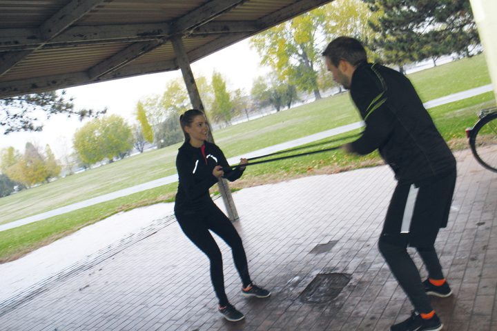 Ein Mann und eine Frau machen Personal Training zu Zwit im Park. Sie ist auf der linken Seite zu sehen und hält ein schwarzes Sportband in beiden Hände. Der Mann steht ihr gegenüber und hält das Band ebenfalls in beiden Händen. Sie ziehen das Band jeweils in ihre Richtung, und bauen somit Spannung auf. Sie tragen beide schwarze Sportkleidung.