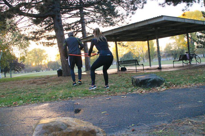 Personal Training zu Zwit im Park. Ein Mann und eine Frau trainieren gemeinsam im Park, bei Sonnenuntergang. Um ihn herum ist ein rotes Sportband gewickelt, welches sie in beiden Händen hält. Er versucht nach vorne zu laufen, während sie ihn mit dem Band davon abhält.