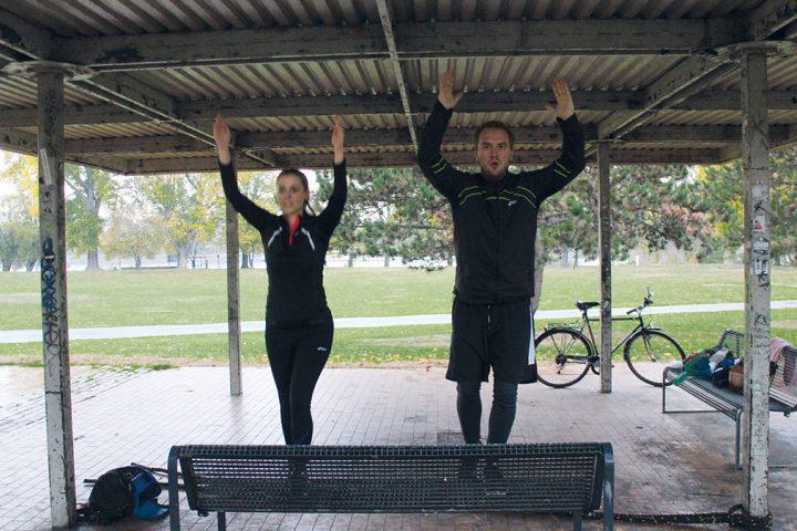 Personal Training zu Zwit im Park. Ein Mann und eine Frau stehen jeweils mit ihrem linken Fuß auf einer Parkbank, mit dem anderen BEin sind sie in der Luft. Sie tragen schwarze Sportkleidung und haben ihre Arme gestreckt über den Kopf gehoben. Ihr Gesichtsausdruck ist angestrengt.