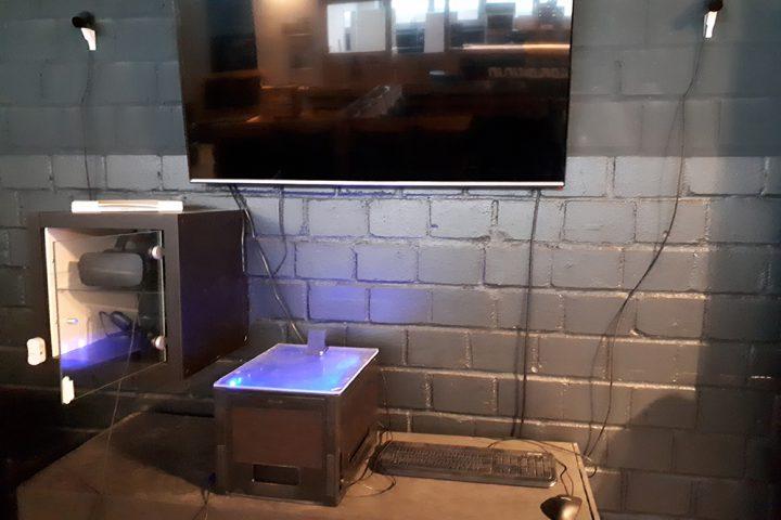 An einer grauen Steinwand hängt ein schwarzer Flachbildschirm. Darunter, auf der linken Seite, hängt ein kleines schwarzes Schränkchen mit einer VR Brille sowie zwei Controllern darin. Die Glastüre steht offen. Auf einem grauen Betonsockel darunter steht eine VR Box sowie eine Computer Tastatur mit Maus. Rechts und links neben dem TV Gerät hängt jeweils eine kleine Lampe.