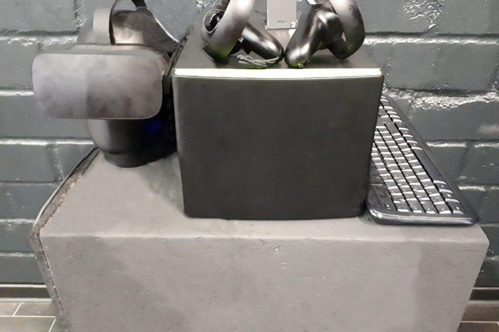 Auf einem hellgraunen Betonsockel befindet sich ein Teil des Equipments für die Virtual Reality. Links steht ein schwarzer Plastikkopf mit der VR Brille. In der Mitte ein dunkelgrauer Kasten mit zwei Controllern darauf. Auf der rechten Seite liegt eine silberfarbene Computer Tastatur.